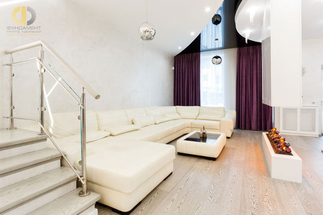 Интерьер современной гостиной с камином и комбинированным потолком