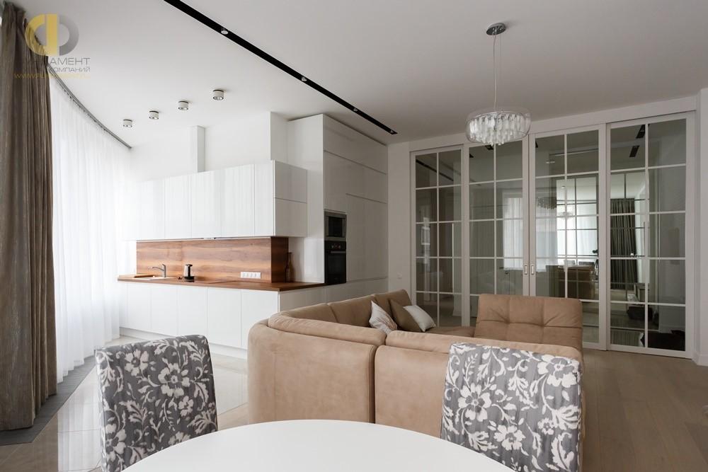 Интерьер многофункциональной гостиной с компактным кухонным блоком